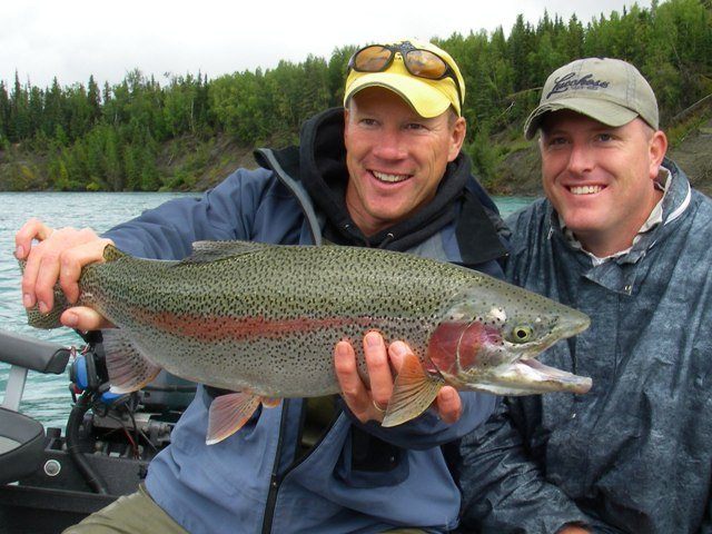 A picture of Jimmie Jack holding up a trophy rainbow trout caught while fishing on the Kenai River.